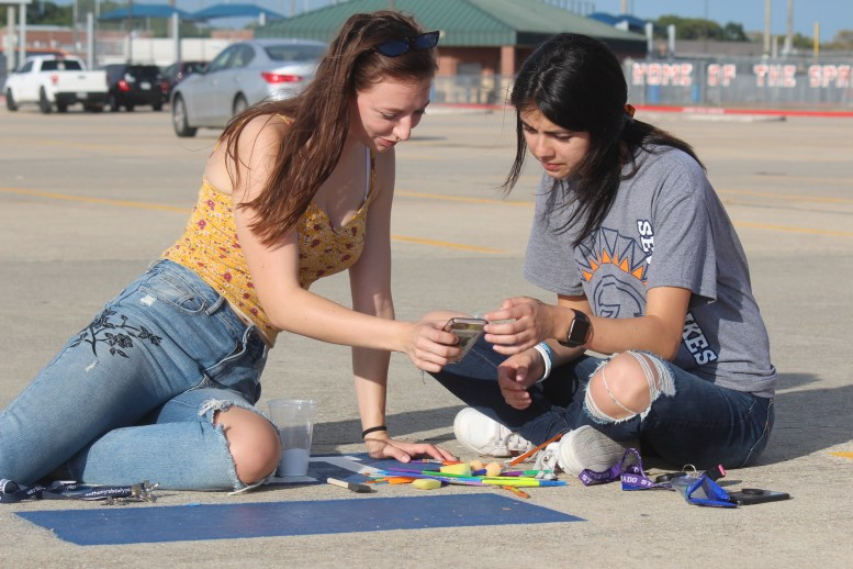 Seniors Bri Johnston and Sofia Davis search up what they want to paint on Johnston's spot. Many students painted their nicknames and a small symbol that represented themselves on their spot.