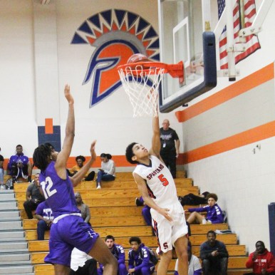 Junior Isaiah Lewis uses layup to win points for the team. The layup is usually made close to the basket, considered the fundamental shot in basketball.