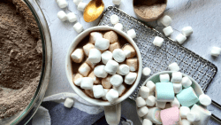 Overhead view of a mug of hot chocolate and marshmallows next to a bowl of hot chocolate mix and a bowl of marshmallows.