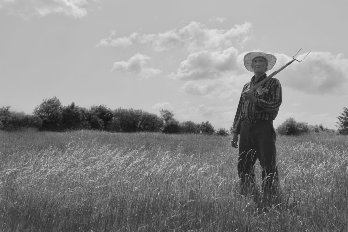 farmer holding fork in field from When All Is Ruin Once Again