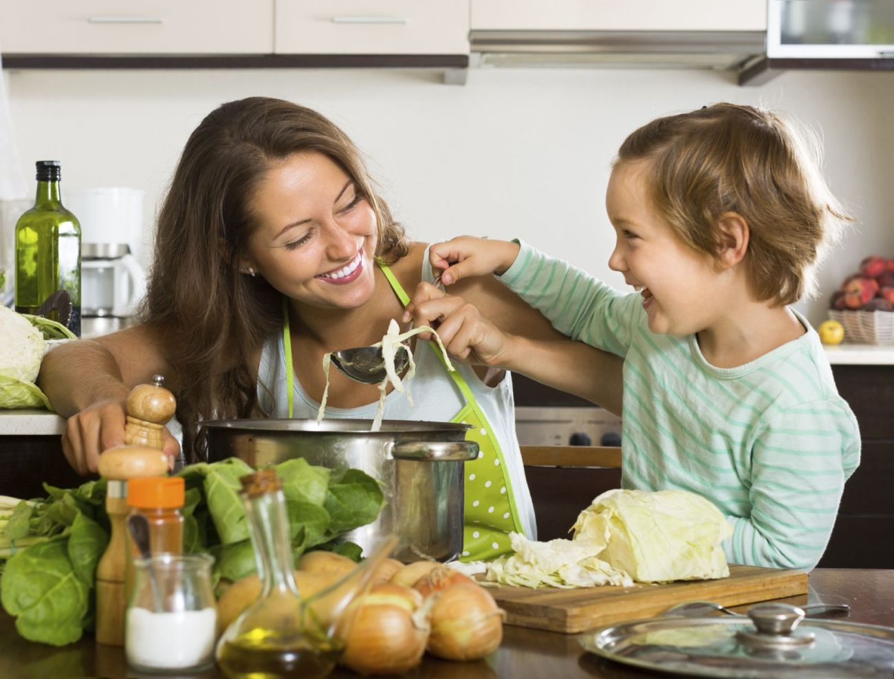 Happy woman with little daughter cooking with vegetables at home kitchen