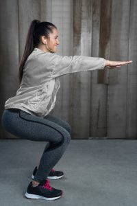 Deep squat. Side view of young beautiful woman in sportswear doing squat against rustic wall