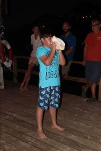 Kid blowing conch shell