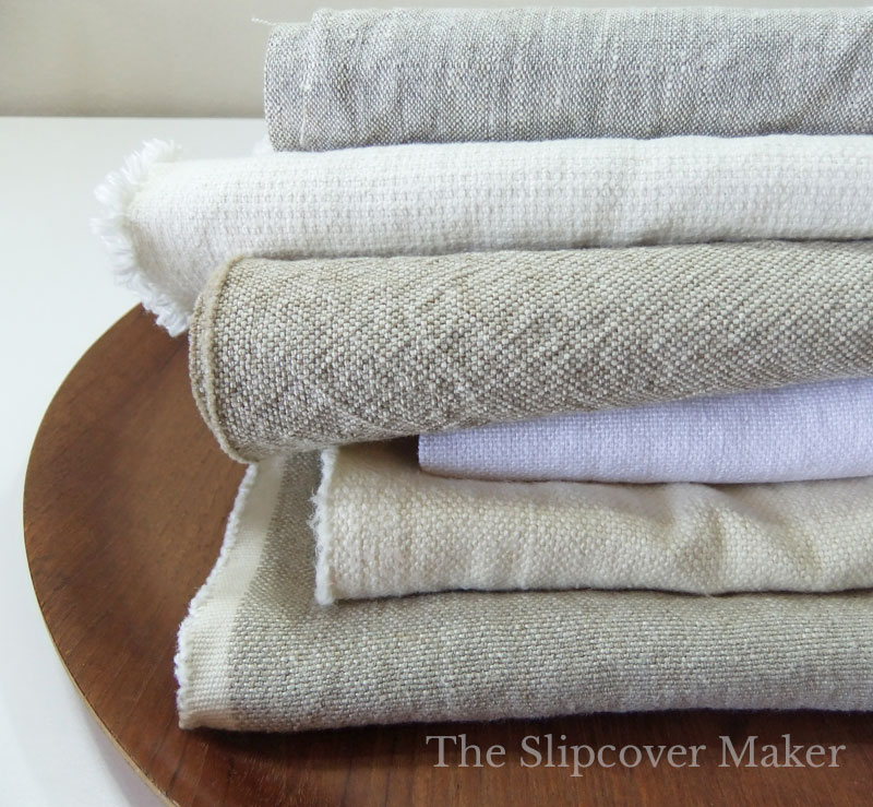 Stack of washable linen and hemp fabrics for slipcovers.