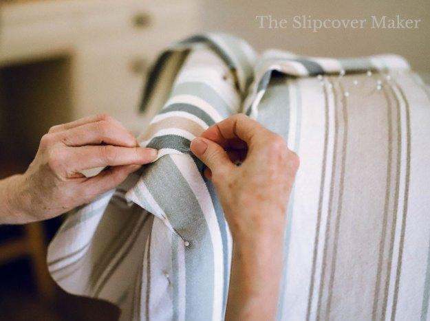 Women's hands pinning pleats on stripe chair.