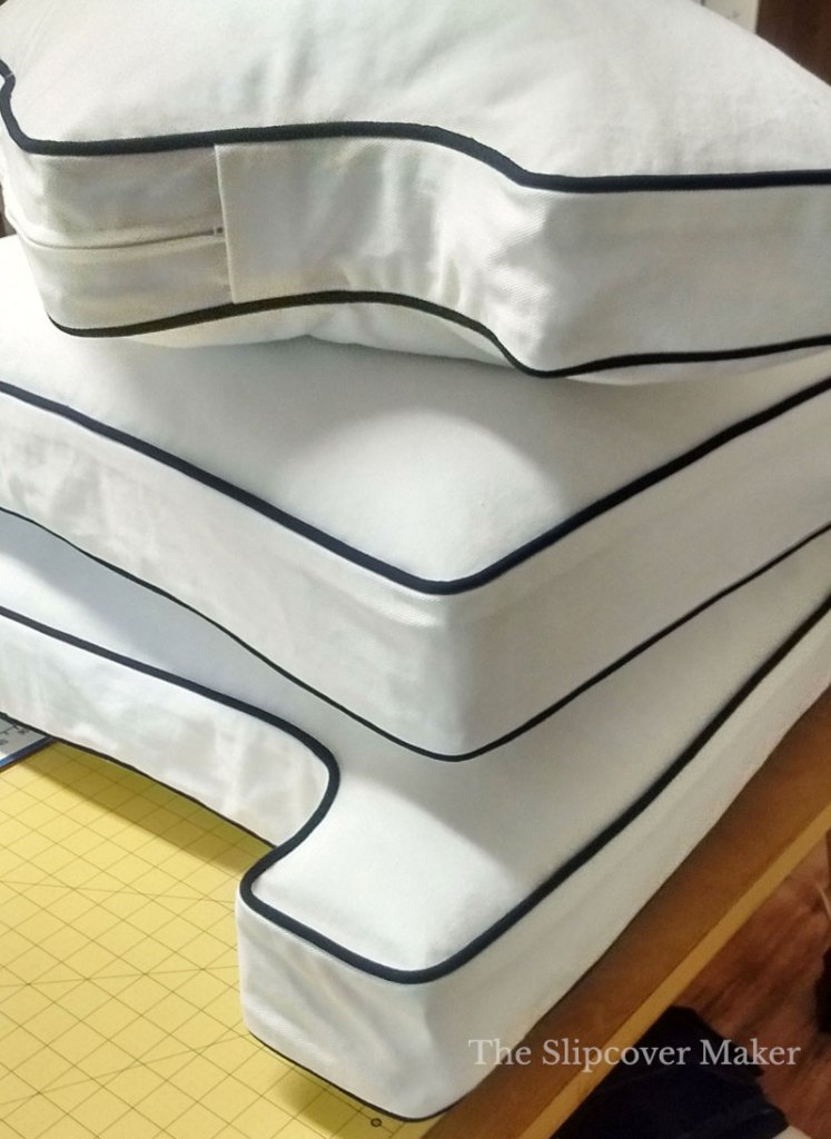 Stack of white box cushions on table.