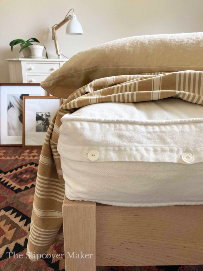 White futon with button cover sitting on bed frame.