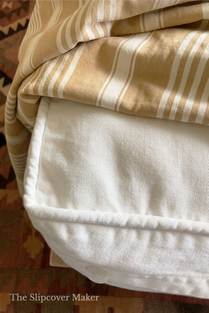 Top of white cushion cover with striped blanket.
