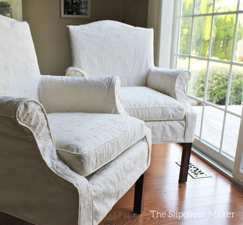 Cream color embroidered slipcovers on dining chairs.