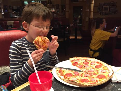 Isaac tucking into a giant pizza for lunch