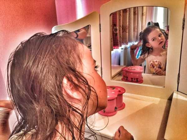 Kara hair brushing at vanity table