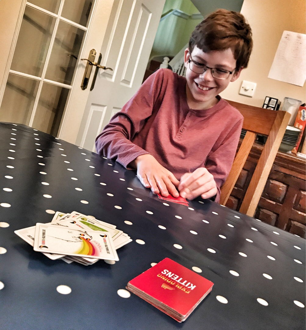 Isaac playing Exploding Kittens card game