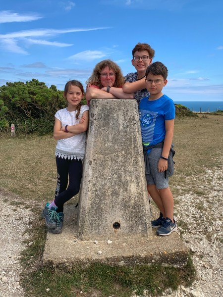 A mother and three kids posing at a trig point