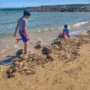 Two boys building sandcastles on a beach