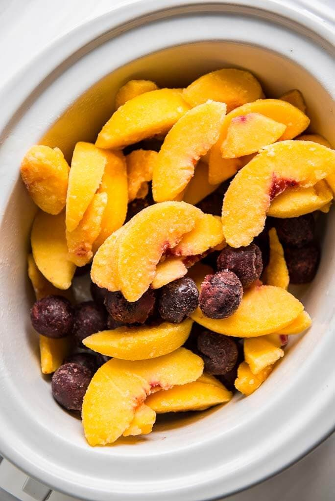 frozen sliced peaches and cherries in a casserole slow cooker