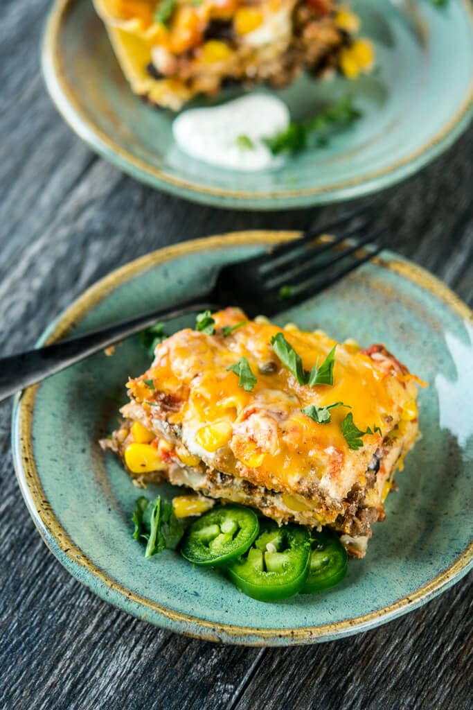 Servings of Slow Cooker Mexican Lasagna on a teal plate with black fork on the side.