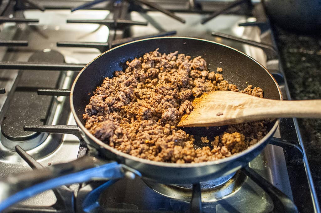 Ground beef browning in a skillet with a wooden spatula on the side, used in Slow Cooker Mexican Lasagna.