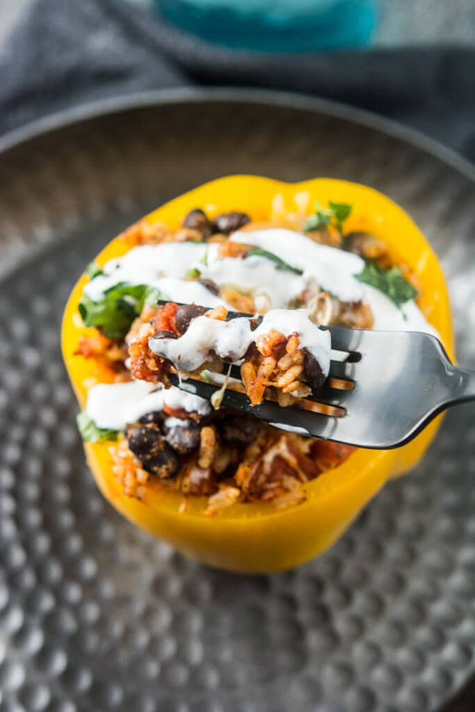 Overhead picture of slow cooker stuffed pepper with a drizzle of sour cream and a sprinkle of cilantro on a black plate with a black fork full of the filling.