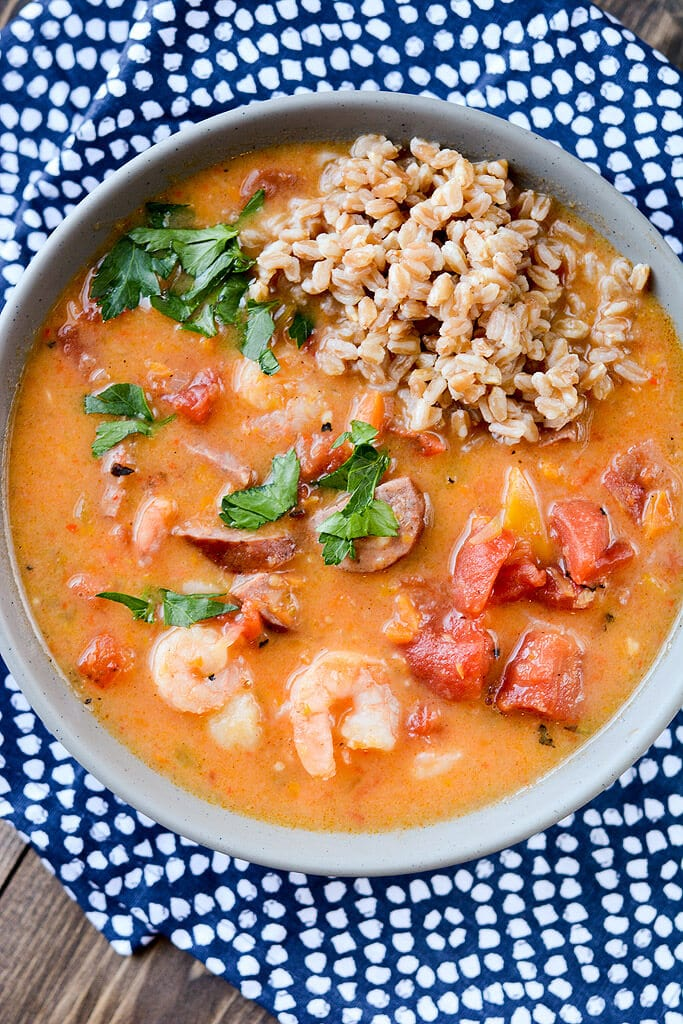 slow cooker spicy gumbo in a gray bowl with a blue dotted napkin