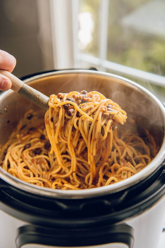 Instant Pot Taco Spaghetti being scooped out of pressure cooker with a spaghetti fork