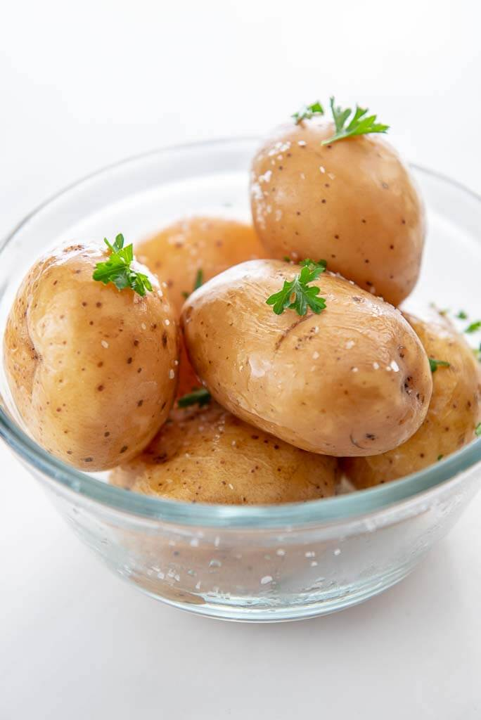several slow cooker baked potatoes in glass bowl