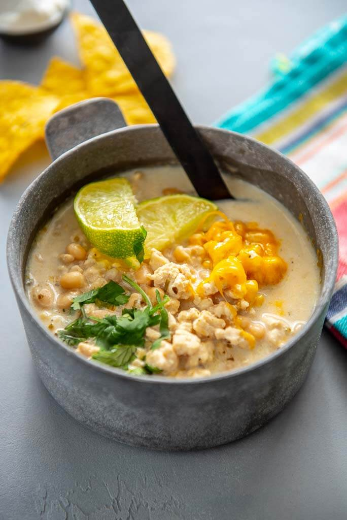 white chicken chili topped with limes and cheese in a metal bowl