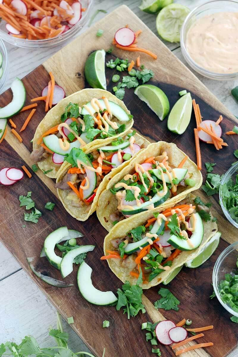 garnished chicken banh mi tacos on wood board with limes and veggies