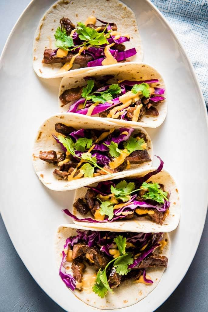Korean beef tacos on a white platter topped with red cabbage and Sriracha mayo