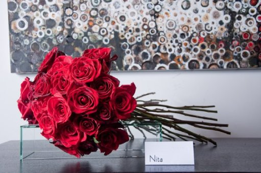 An arrangement of red roses in front of the painting Ishmael by Randall Stoltzfus