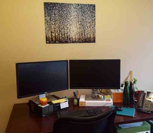 A Poster of Randall Stolzfus' poster of his painting Ida Grove hangs over a desk
