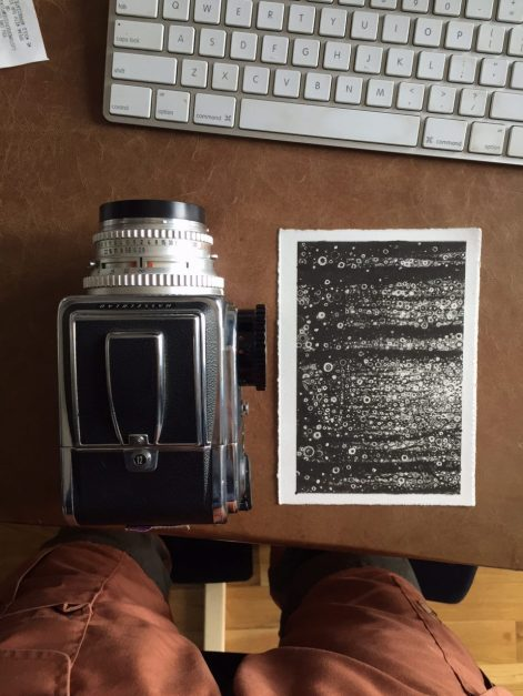 Black, white, and silver 'Wisdom' print by Randall Stoltzfus on desk beside Hasselblad camera and computer keyboard