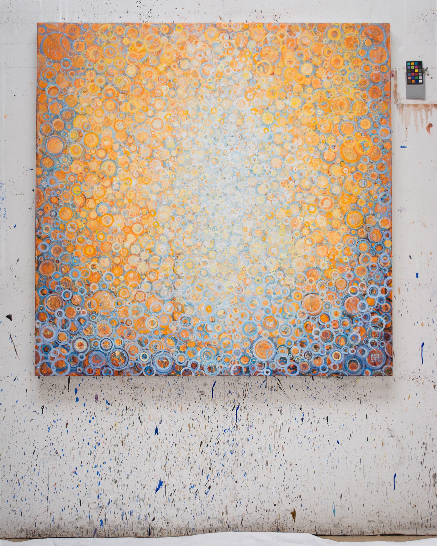 """The painting Orange and blue   Completed commissioned painting titled """"Seek"""" by Randall Stoltzfus hangs on paint-spattered wall of the artist's Brooklyn studio"""