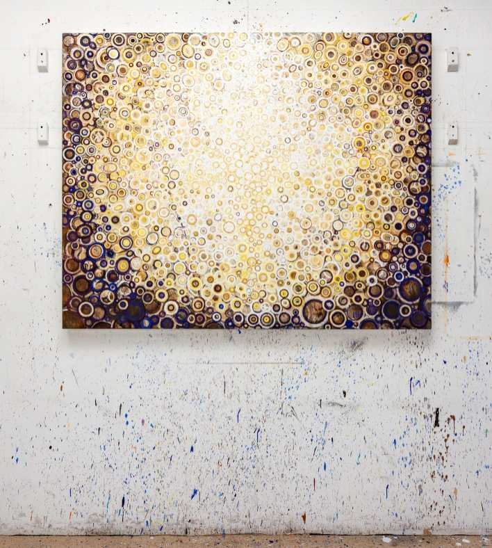 Gold, White and a Touch of Cobalt Violet | The painting titled Corona by Randall Stoltzfus hangs on a paint spattered wall in the artist's Brooklyn studio