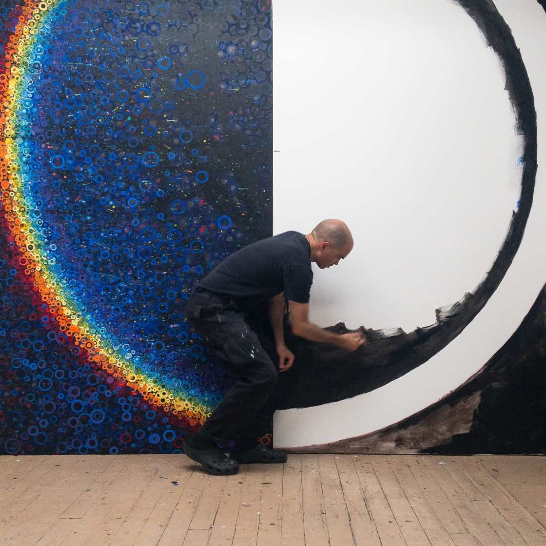 Randall Stoltzfus beginning work on the second half of an 8 by 10 ft rainbow colored canvas