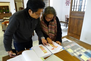 Dr. Yamazaki and Yoshiko Wada look over swatches of natural dyes