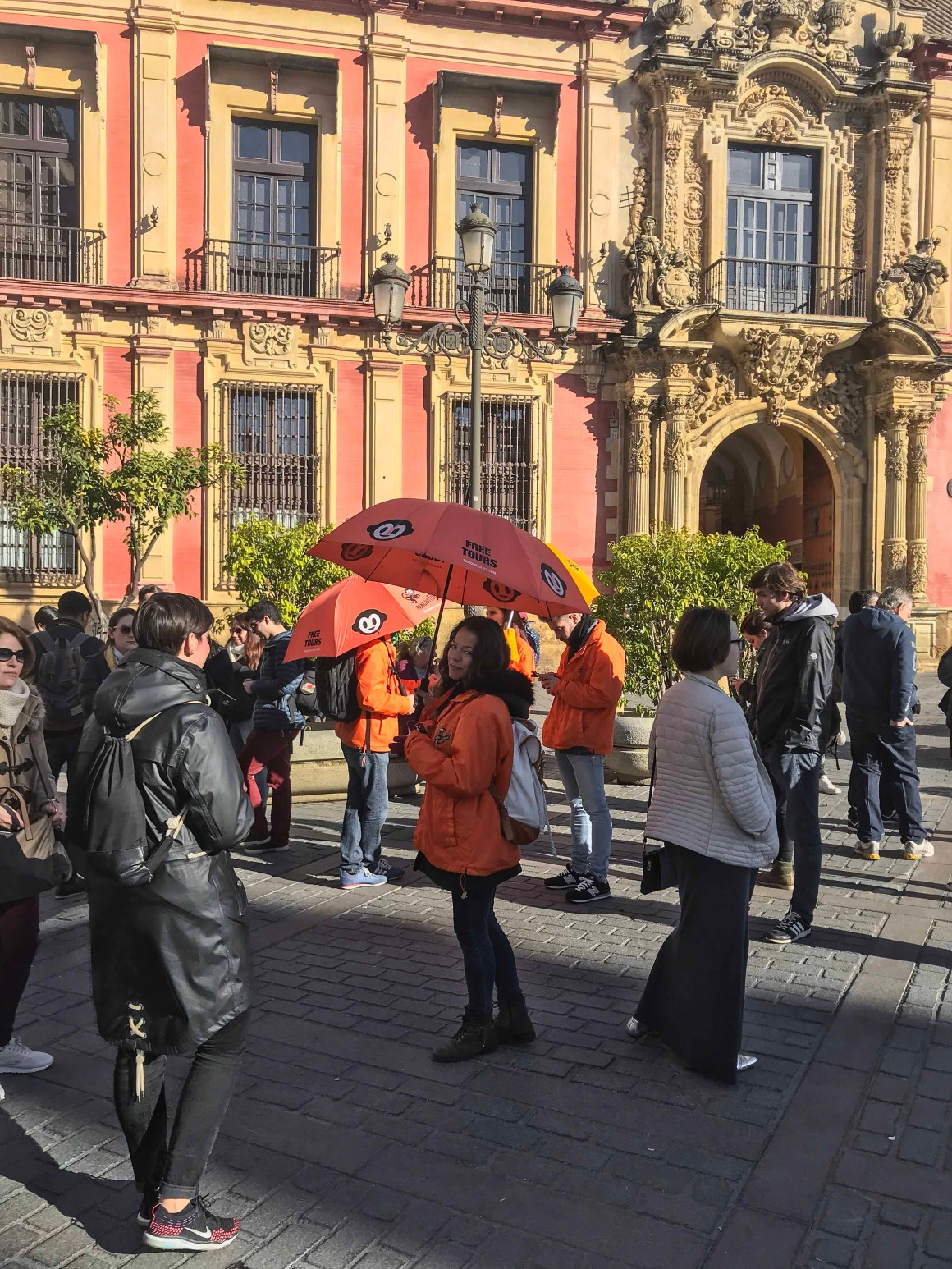 People in the streets, orange dressed girl with umbrella