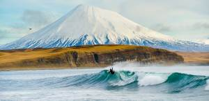 a pro surfer catching a wave in Iceland