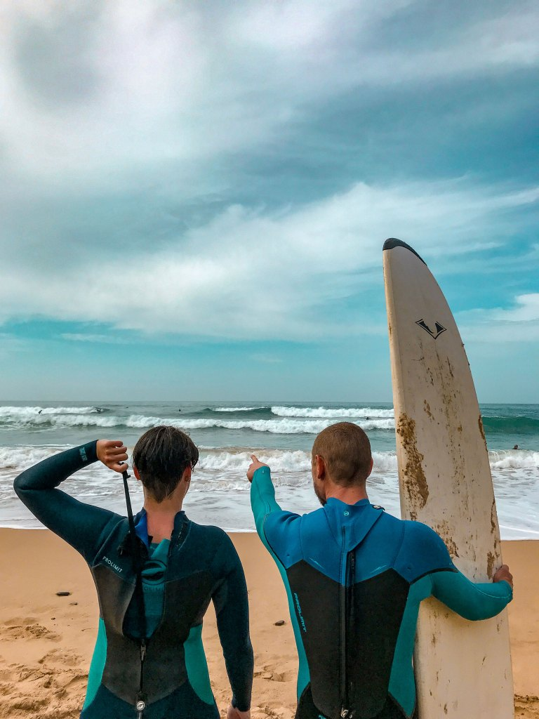two surfers pointing the waves