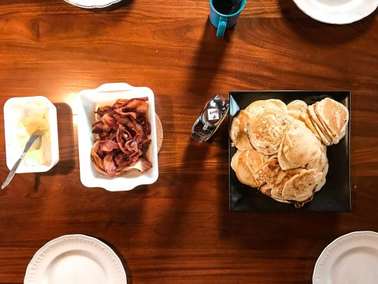 pancakes and bacon on a wooden table