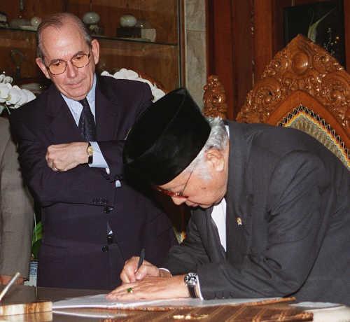 """IMF 양해각서에 서명하는 인도네시아 수하르토 대통령과 이를 바라보는 미셸 캉드쉬 IMF 총재. 사진이 논란을 빚자 캉드쉬는 """"사진을 찍는지 몰랐다""""고 해명했다. (1998년 1월 15일)"""