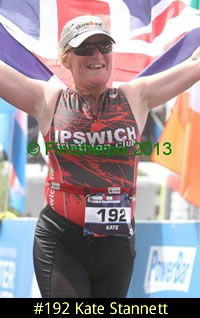 Photo of 2013 Ironman 70.3 World Championship competitor Kate Stannett happily carries the British flag as she crosses the finish line.