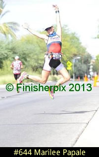 Photo of 2013 Ironman 70.3 World Championship competitor Marilee Papale jumps for joy on the run course.