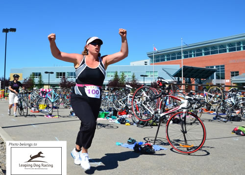 Color photo of woman with hands raised in happiness participating in a triathlon.