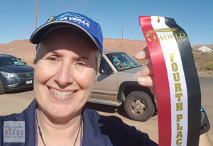 Color photo of Bonnie Parrish-Kell with her 4th place ribbon in the 2016 Huntsman World Senior Games 1500 meter race walk.