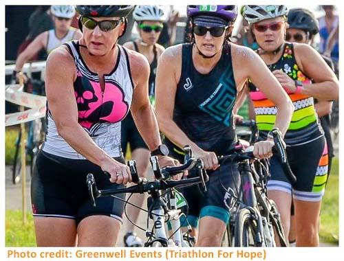 3 female triathletes with bikes