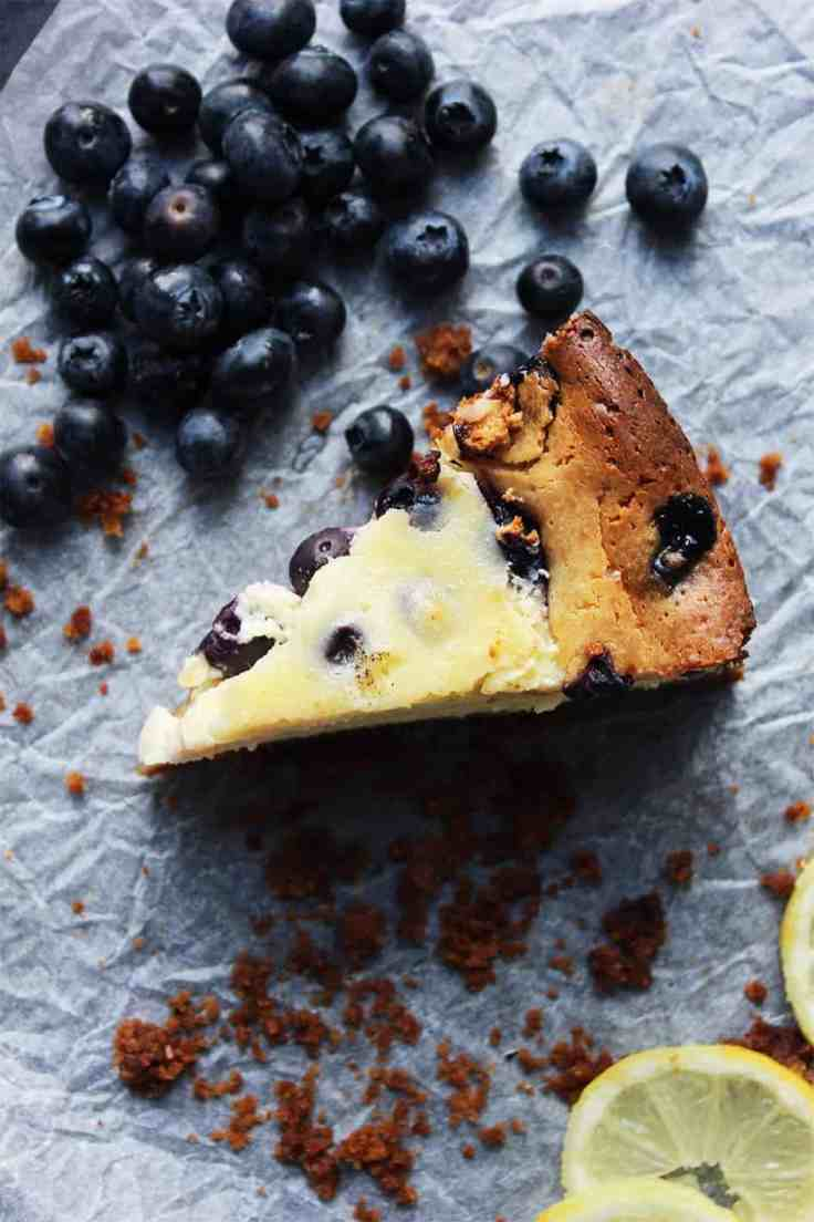 A slice of Baked Lemon & Blueberry Cheesecake on a piece of parchment
