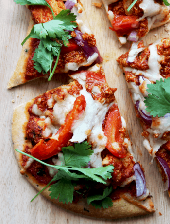 Naan bread pizza on a wooden chopping board