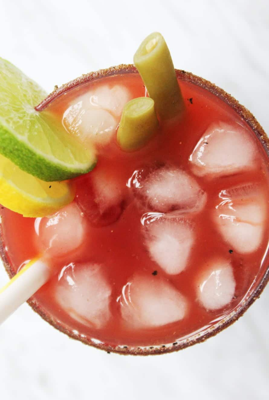 Close up top shot of a caesar drink, garnished with lemon , lime and pickled beans