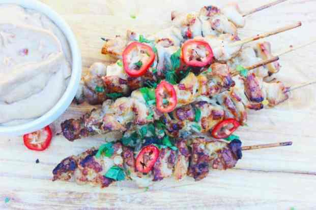 skewers of crispy chicken satay with peanut dipping sauce on a wooden serving board