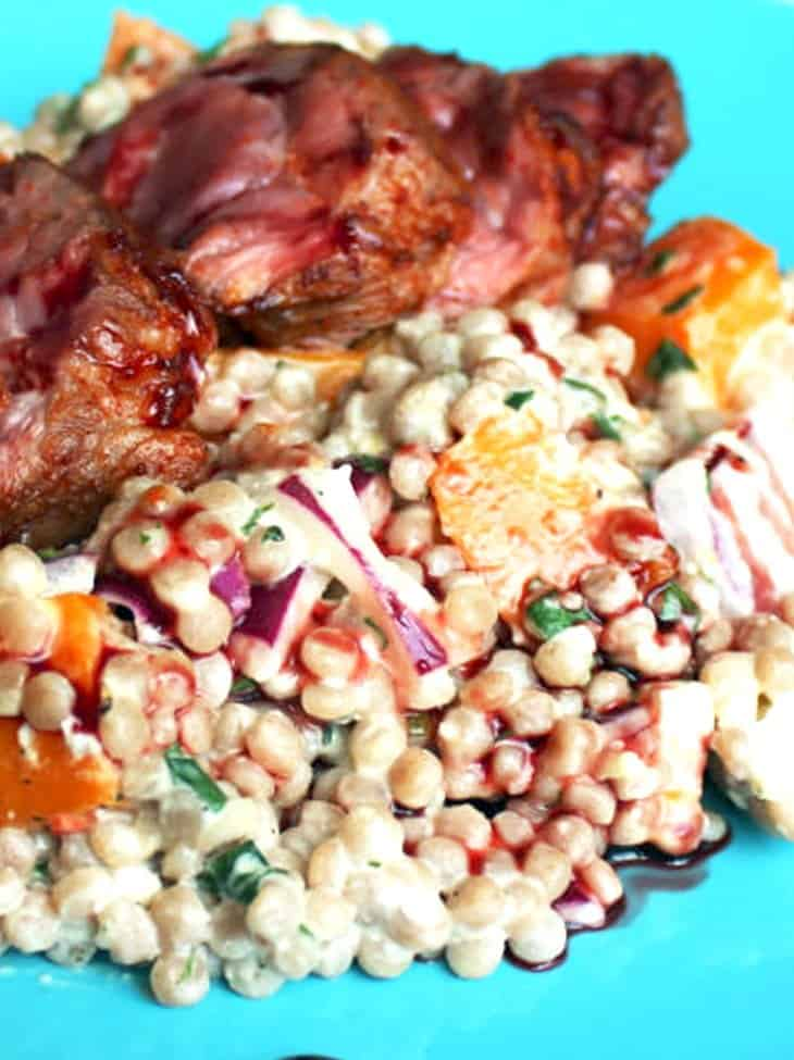 Giant couscous salad on a blue plate, topped with sliced lamb neck